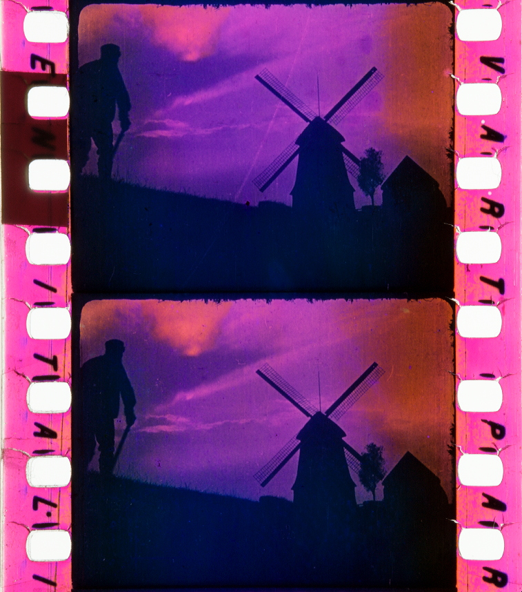 A blue, purple, and pink toned still frame of a film. Frame depicts a shadow of a man standing and facing a windmill and house, with a tree in between.
